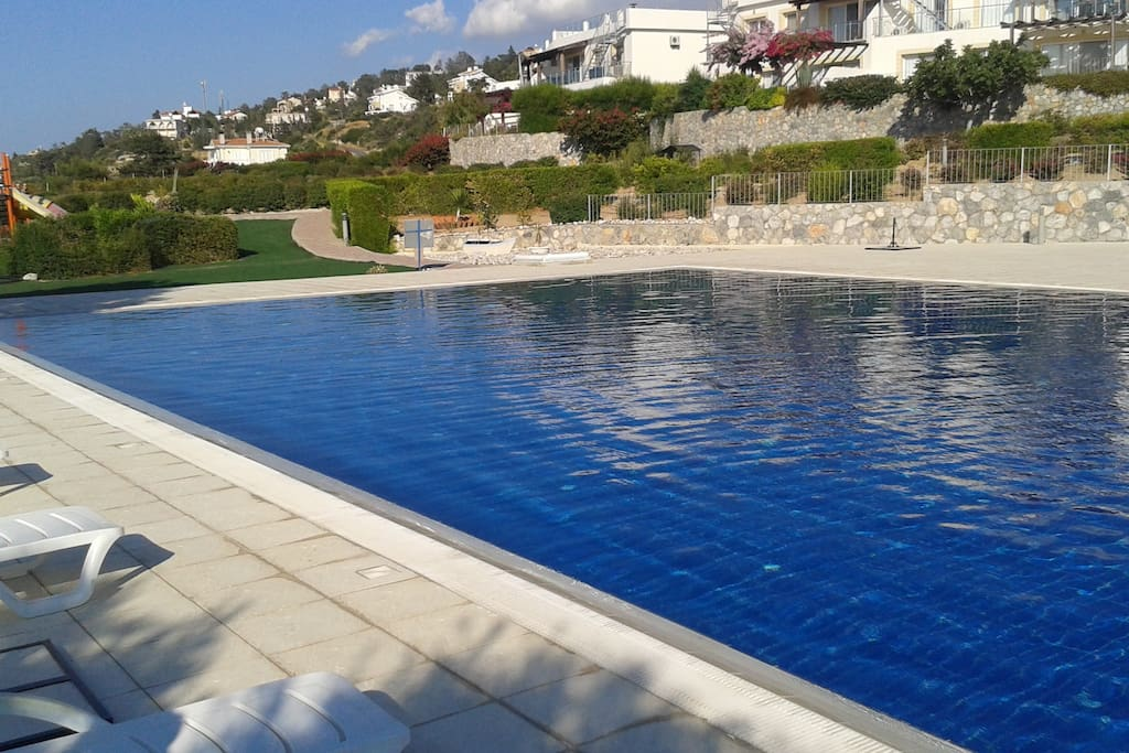 Relax by the large swimming pool with loungers & adjacent kids' pool
