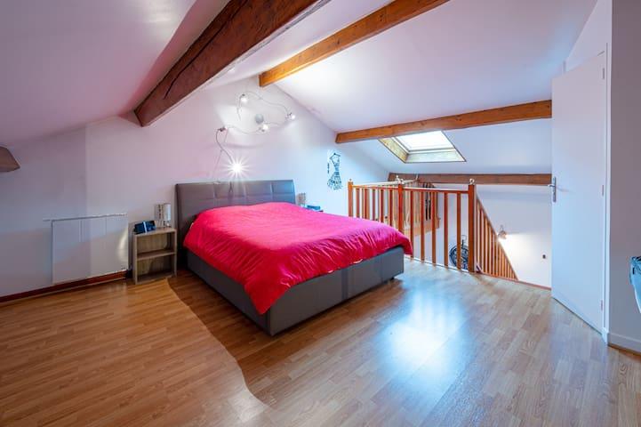 Un chambre à coucher en mezzanine douillette pour 2 personnes et un lit parapluie