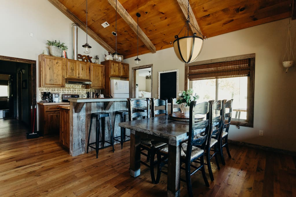 Front room of the cabin is the great room featuring the kitchen, dining, and living space of the cabin.  Rustic walnut cabinets, custom barnwood island, apron front farm sink, and hand poured concrete bar top blend together to make this beautiful kitchen space.
