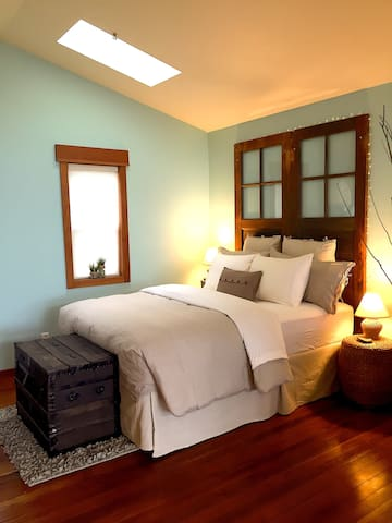 Reclaimed barn doors create the headboard, a century-old trunk of a Czech immigrant makes the foot of the bed.