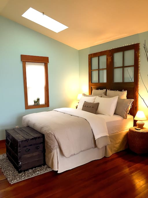 Reclaimed barn doors make the headboard, a century-old trunk of a Czech immigrant makes the foot of the bed.