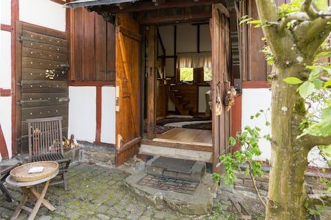 történelmi, félig fából készült ház az erdő szélén