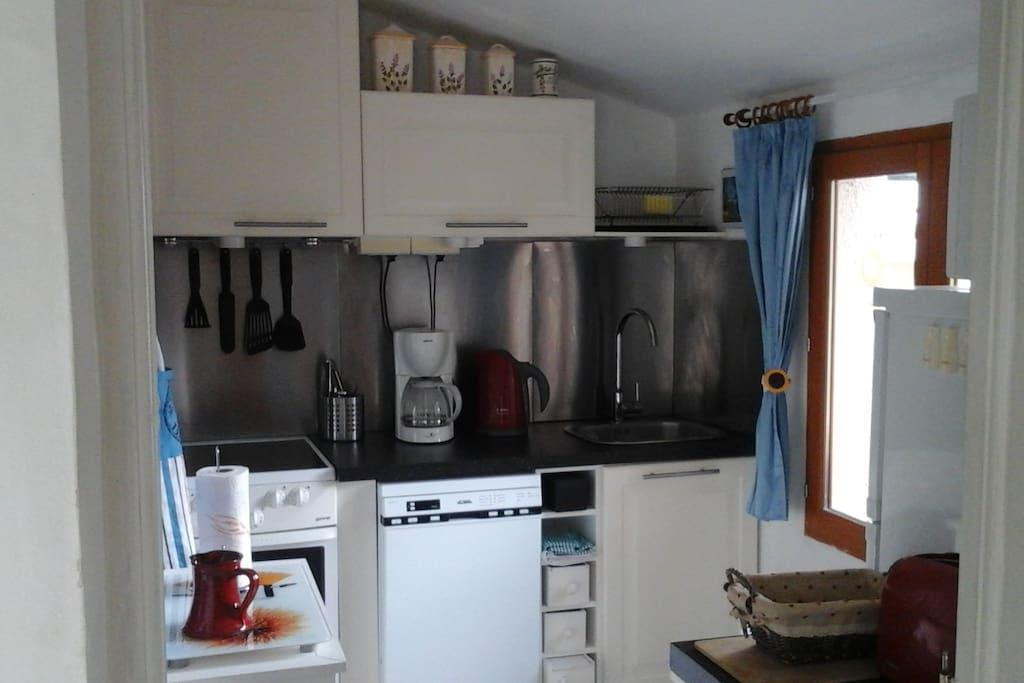 La petite cuisine équipée avec des plaques vitrocéramuques, lave-vaisselle, réfrigérateur-freezer, micro-onde, four.