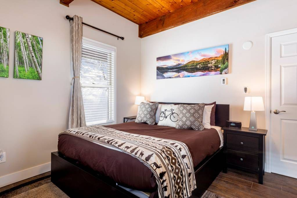 Queen bedroom decorated for nature and adventure. Luxury linens and tuft and needle memory foam mattress will make this a great place to relax after a hard day biking or skiing.