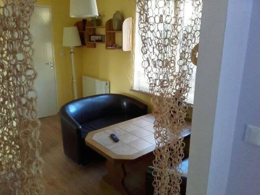 Salonik z rozkładaną i podwyższaną ławą, dwie kanapy i dwie pufy