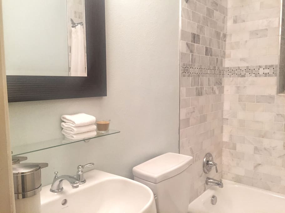 Guest Bathroom - small, but clean and well-appointed, featuring a tub/shower with Bianco Cararra Italian marble surround