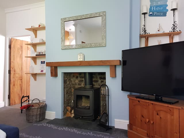 """Warm and cosy living room with 49"""" smart TV - log in to enjoy all your favourite streaming services."""