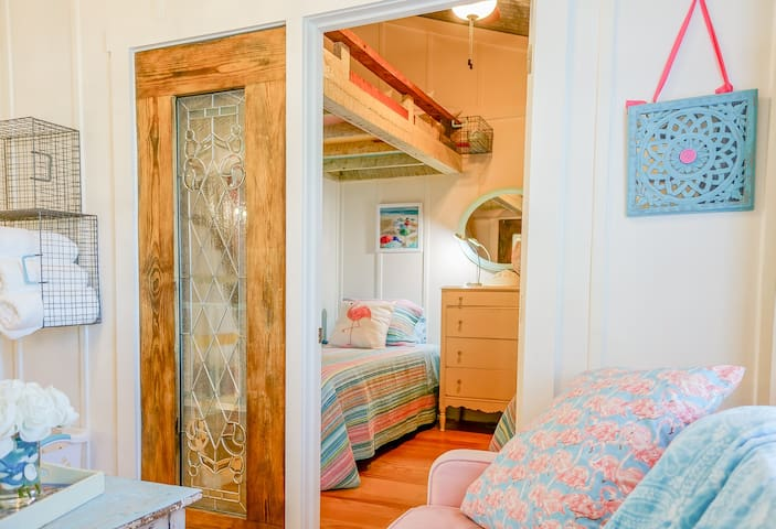 """Everything about this home is unique & custom built! """"Flamingo"""" is the upstairs corner bedroom! 3 XL Twin beds, two lower, one bunk, lower beds convert to KING but mind you don't scratch the floors! A full size fold down is just outside the room!"""