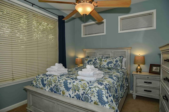 The guest bedroom has a queen bed with a pillow-top mattress and room darkening curtains