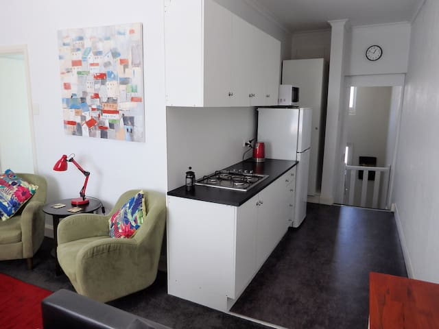 Neat, clean kitchenette with pots, pans and gas cooktop.
