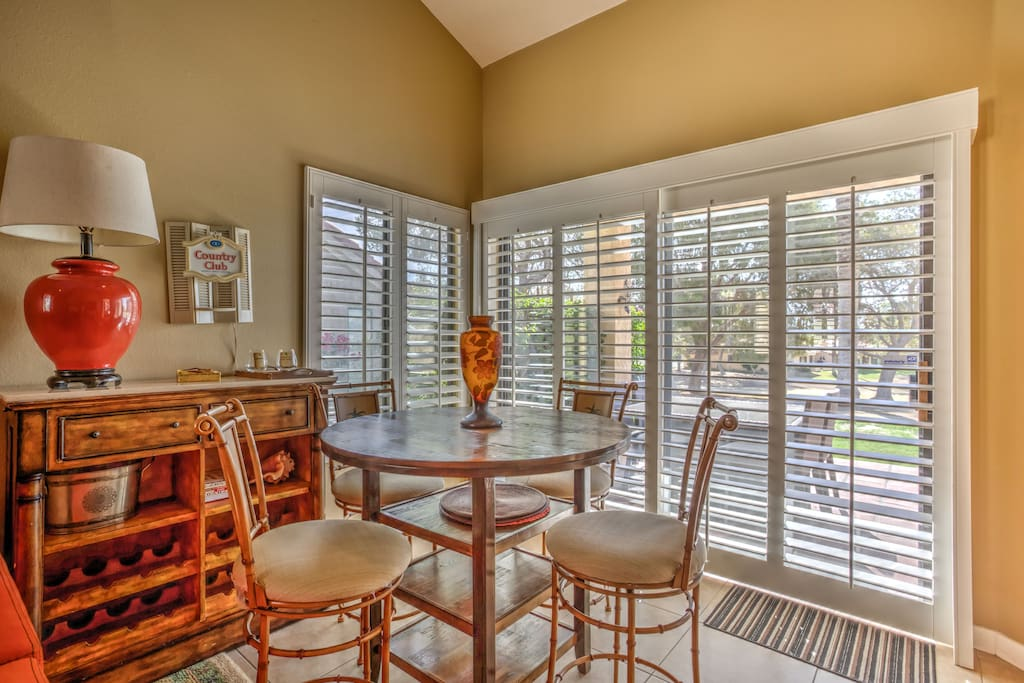 four seat dining with plantation shutters and view of fairway.