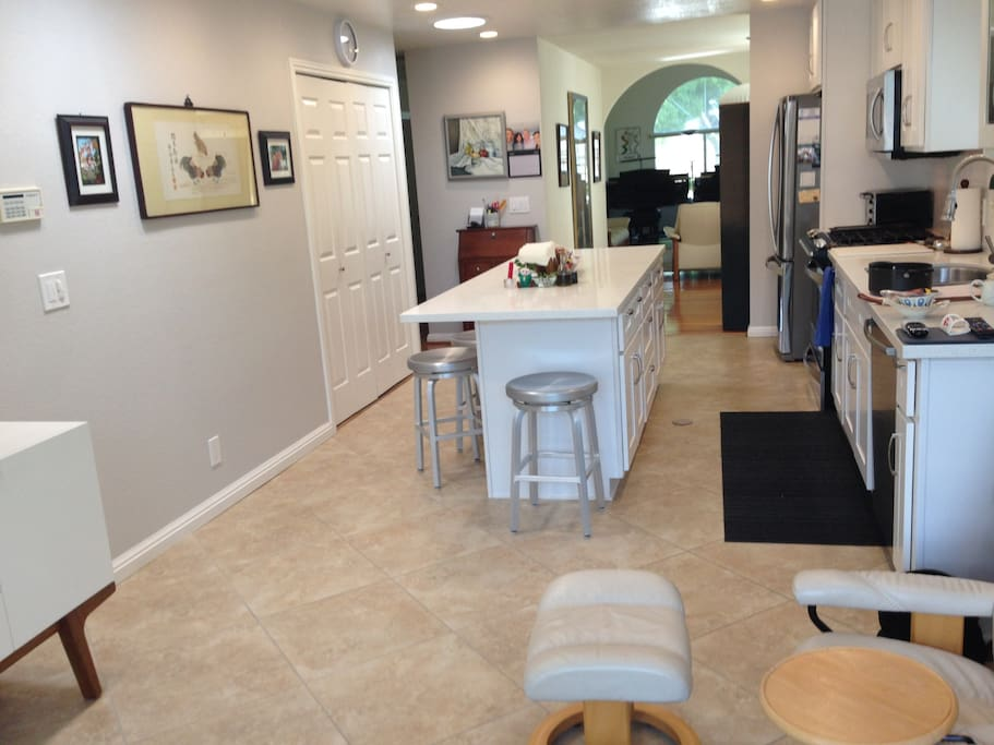 Remodeled kitchen/family room with gas stove, large island, TV and two easy chairs.