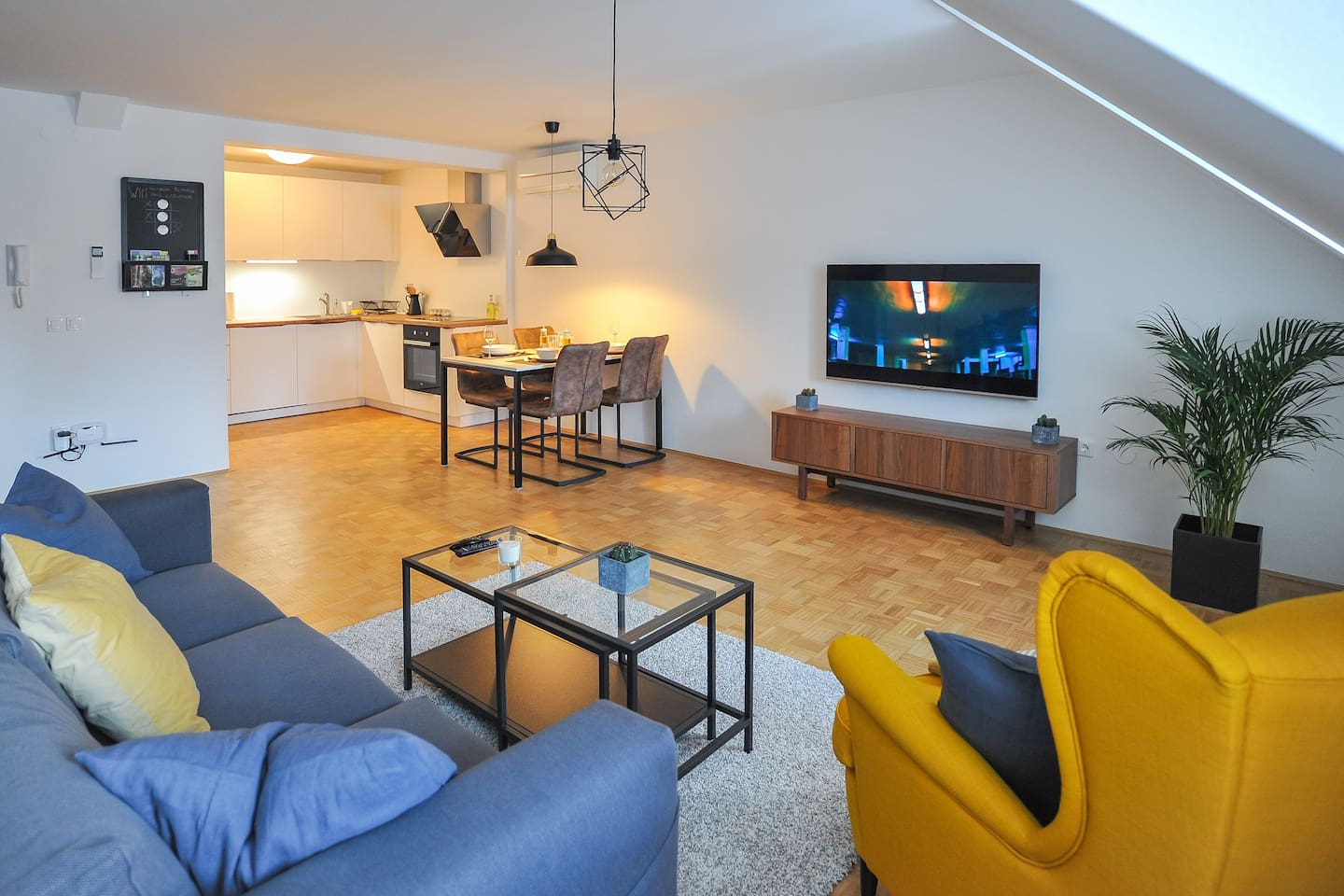 Big, spacious living room with a 55'' flat TV and dining area