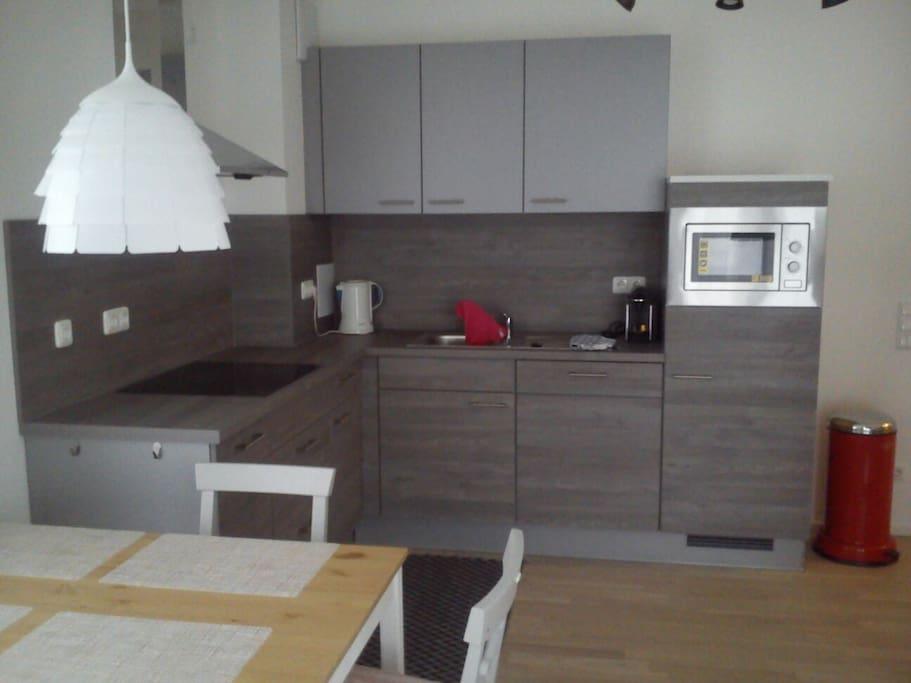 Vollstängig eingerichtete Küche mit Herd, Microwelle und Spülmaschine