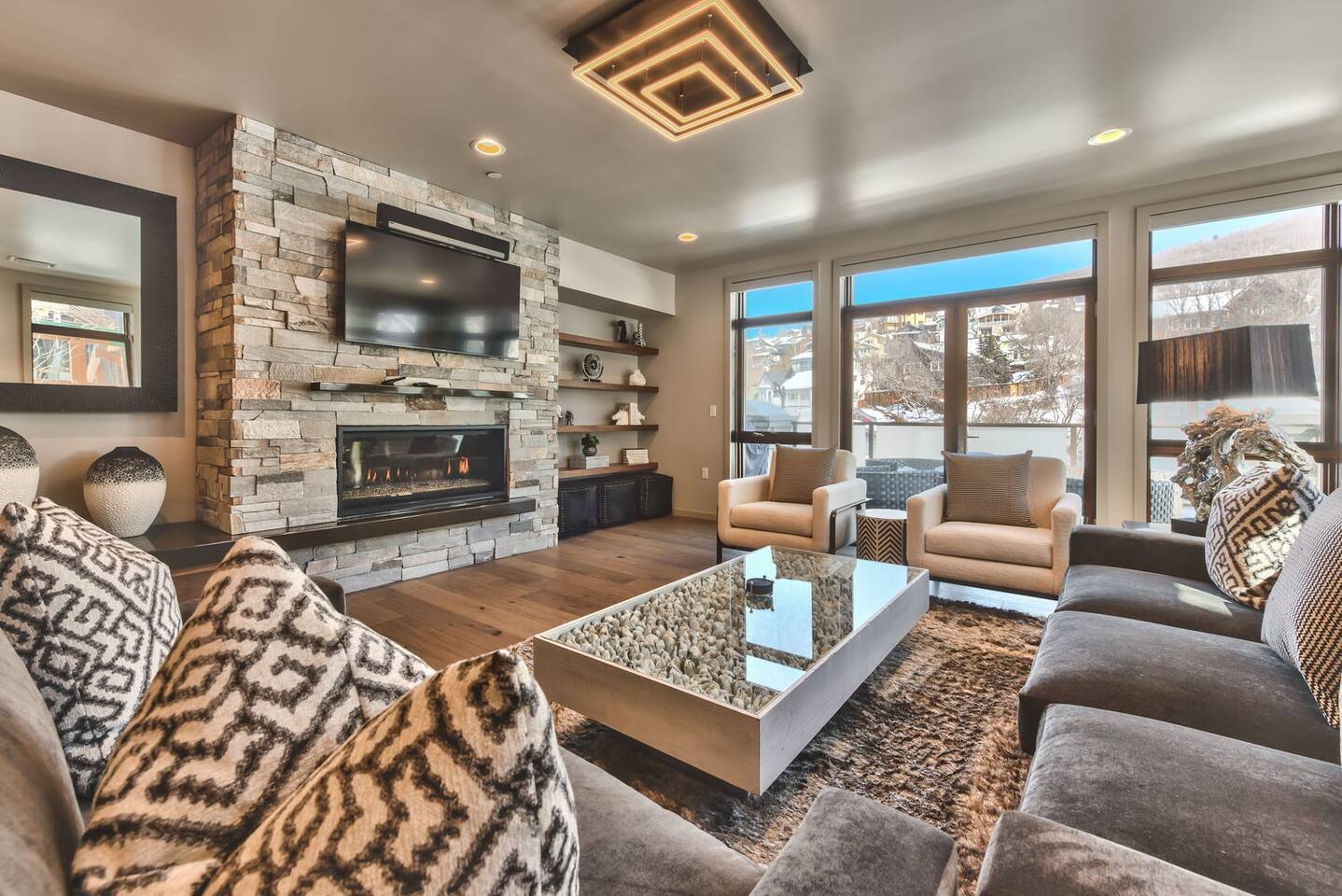 "Professionally Decorated Living Room with 60"" Smart TV, Sonos PlayBar, Comfortable Furnishings, Gas Fireplace, and a Private Deck Overlooking Main Street"