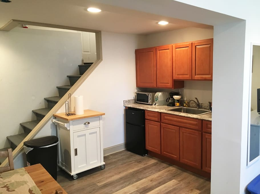 Studio apartment includes a small kitchen that features a sink, mini-fridge, toaster oven, hot plate and small coffee maker