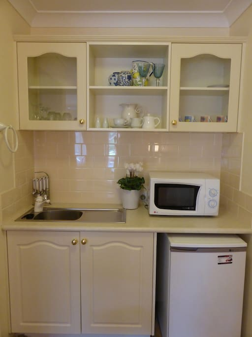 Kitchenette including microwave and bar fridge, crockery and cutlery