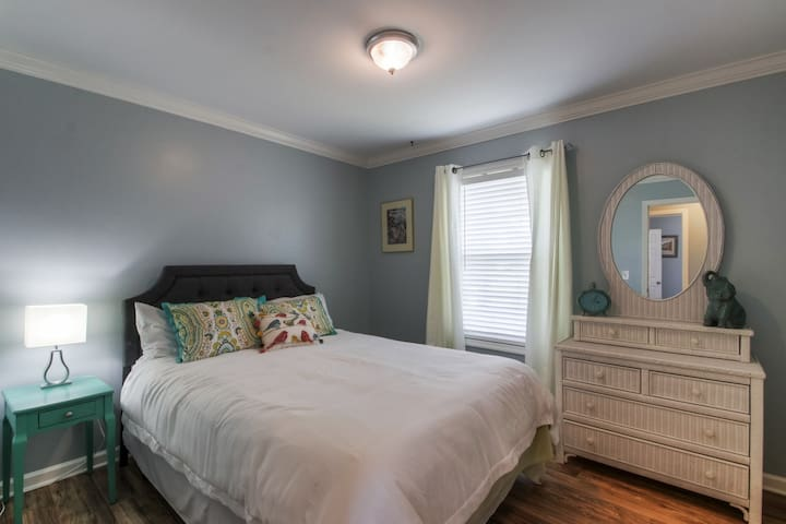 Queen bed with vintage wicker dresser. In the closet is a new play-n-pack and high chair if you need them.