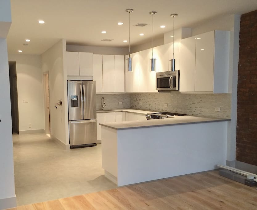 kitchen features bright white lacquer cabinets, quartz countertop, high end stainless steel appliances, undercabinet lighting, and beautiful glass and steel mosaic backsplash