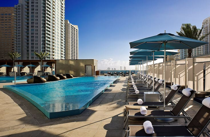 Modern Space with a Private Balcony, Floor-to-Ceiling Windows, and Stunning Water Views | Shared Rooftop Pools + On-Site Spa