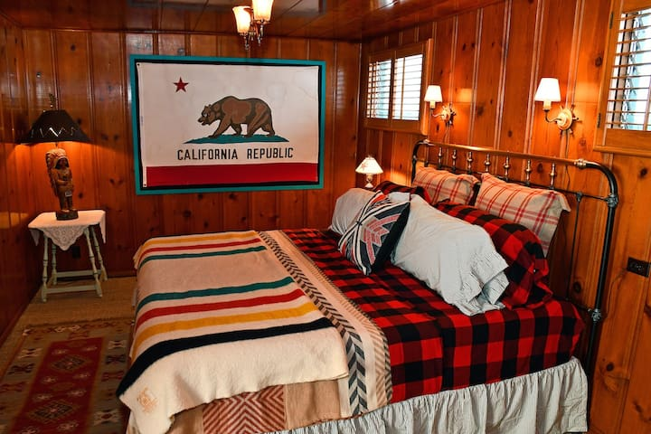 (# 1) master bedroom w/ king-sized bed on vintage frame, more cabin-style warm-yellow knotty pine all around and above