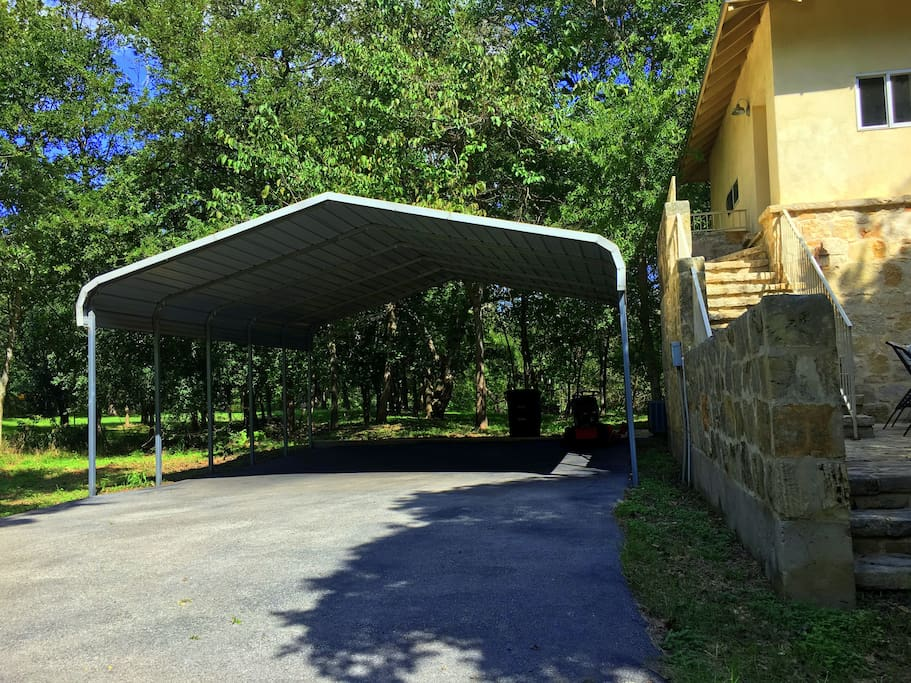 A carport is located right next to the house, and extra space for vehicles is also available in the driveway