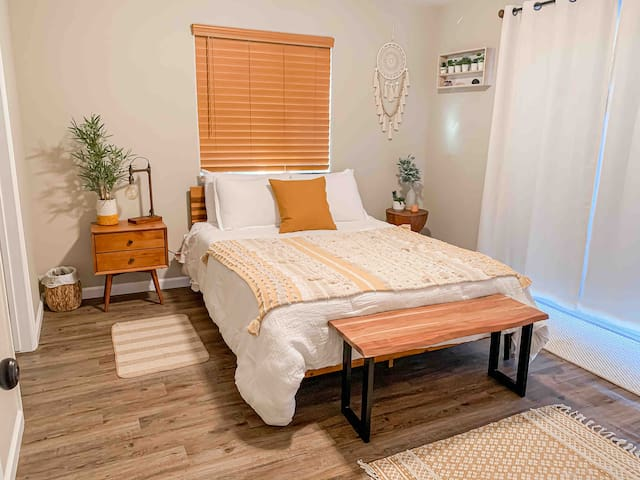 Main bedroom features a queen sized bed, attached restroom, & sliding doors leading to the backyard patio.