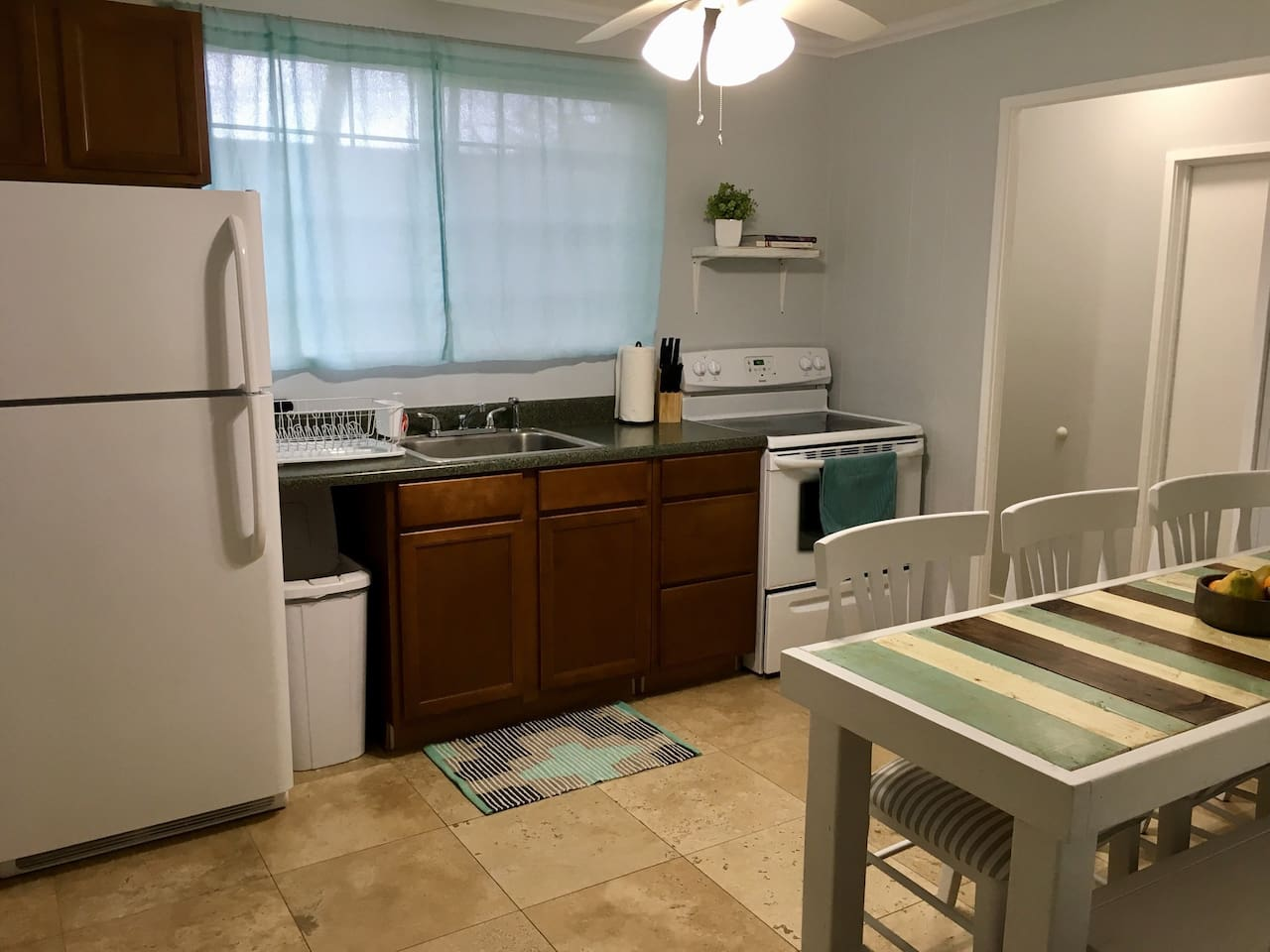 Kitchen with large fridge, oven with ceramic stovetop, knife set, kitchen table that seats 6