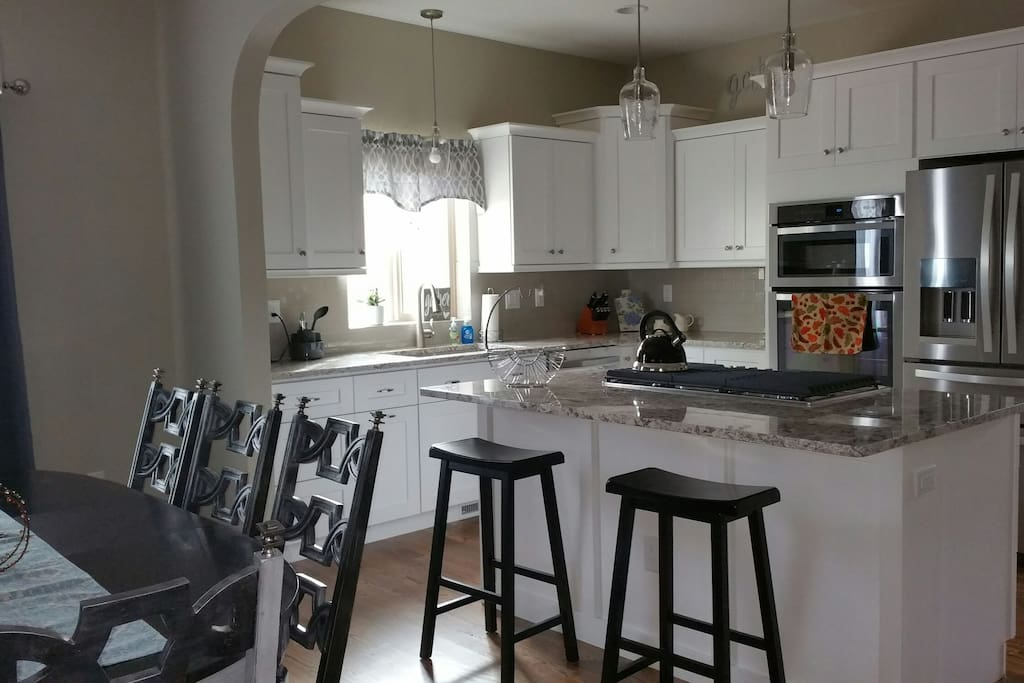 Kitchen with gas cooktop in island, granite counter throughout and stainless appliances.
