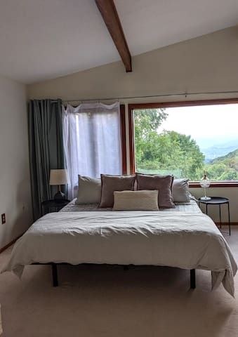 Master Bedroom features vaulted ceilings and an ensuite bathroom.  The room has a a gorgous wall of windows overlooking the mountains and back deck.  Black out curtains are hung as well for sleepy mornings!