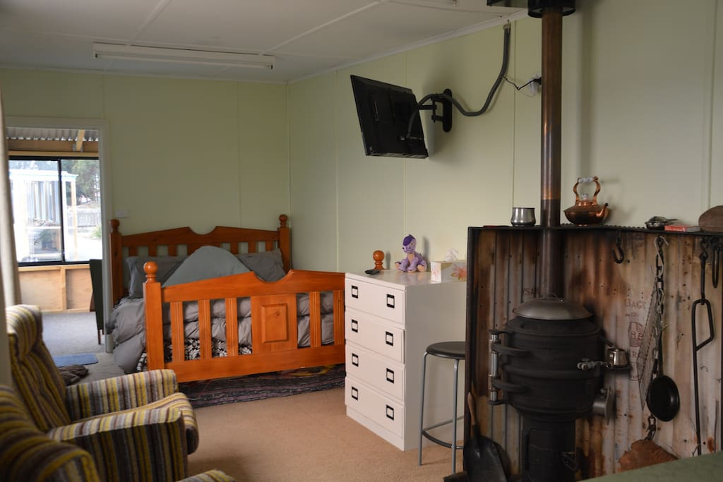 Open plan studio with Queen bed, TV, pot belly fire, kitchenette, comfy chairs by the fire.