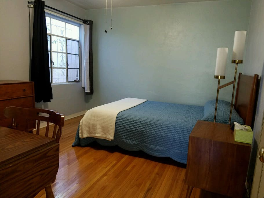 Spacious bedroom featuring natural wood furniture and hardwood floors.
