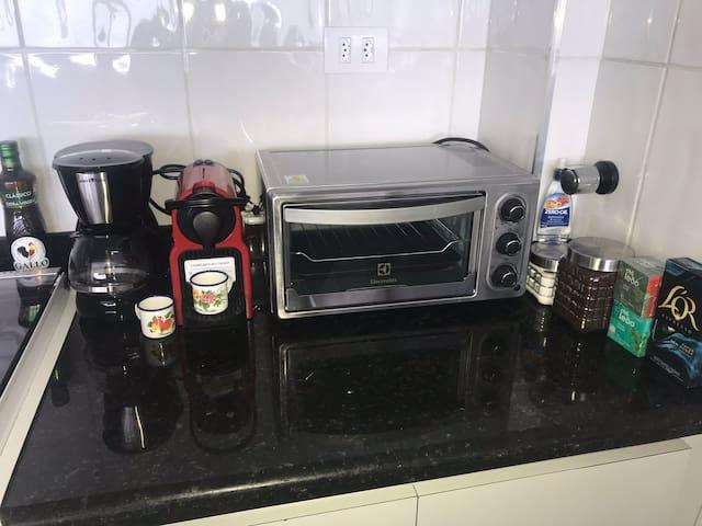 Cafeteira tradicional, cafeteira Nespresso, forno elétrico e amenidades (café em pó e em cápsula, açúcar, adoçante e chás)