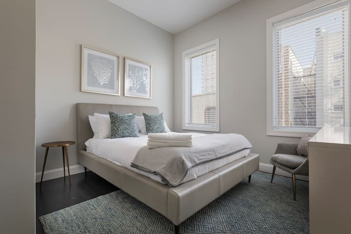 The queen-size bed in the master bedroom has a super-comfortable Leesa memory foam mattress and is layered with crisp, white linens, a down comforter and coverlet. This bedroom has an elegant en suite bathroom.