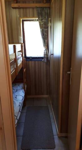La chambre avec les lits superposés (penderie + volet + moustiquaire)
