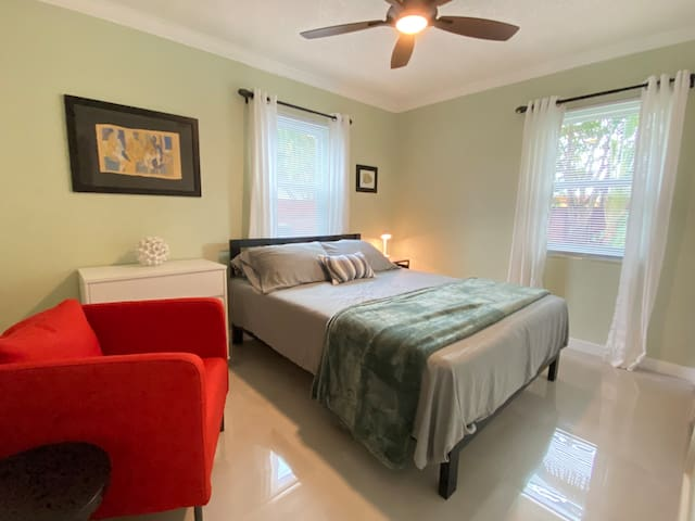 Queen bed with reading chair and garden view. (A twin rollaway bed is stored in the closet.)