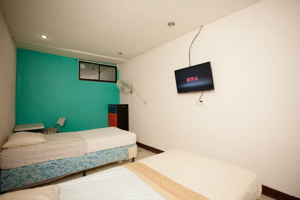 room with two indivuduals bed, tv and AC