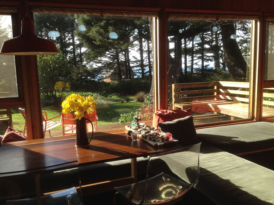 Dining/Living Area facing west towards the ocean - cabin is surrounded by Sitka trees and the ocean is visible thru the trees.