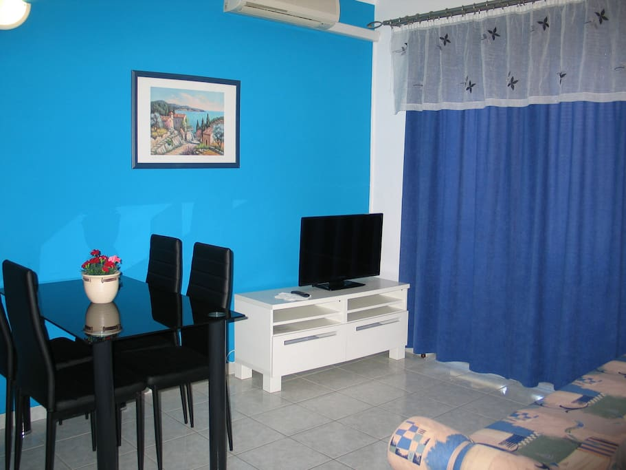 table, 4 chairs, sofa and TV with access to the balcony, air condition