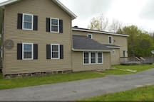This is the right side of the house showing the driveway with plenty of parking and the large deck with the entrance to the guest suite door.