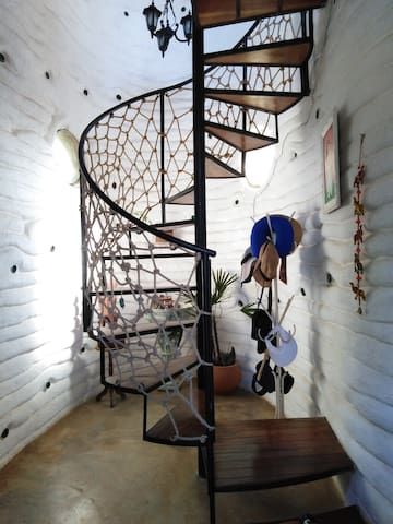 Hall de entrada com espaço de leitura; escada de acesso à suíte