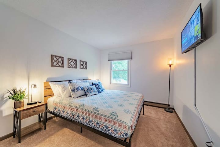 """Queen bedroom with 6 pillows, phone charger ports built into bedside tables, 32"""" Roku TV and blackout blinds."""