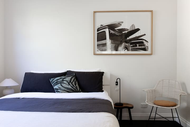 The Retreat Queen Bedroom - with a nod to the Gunnamatta surfers of yesteryear.