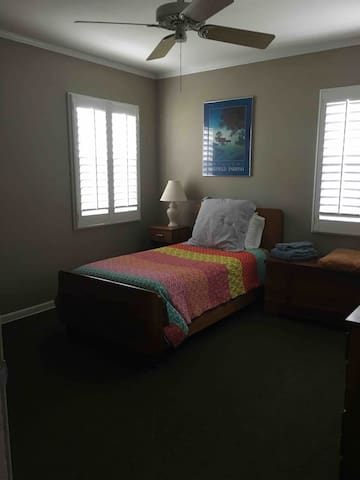 Twin Bed in spacious bedroom with 2 windows.  Shutters can be closed to make room darker for sleeping!