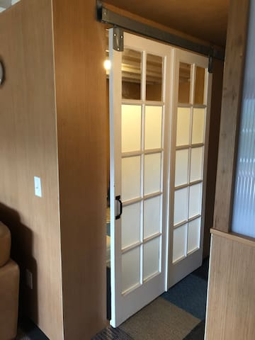 Barn style door into the tv room/guest bedroom. Fold out couch and smart tv inside!