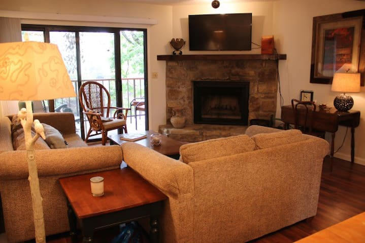 """49"""" TV over fireplace and view of living room balcony"""