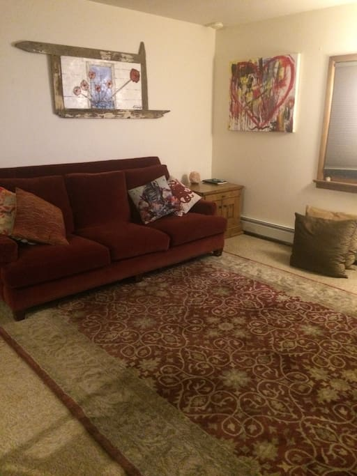 Living room with comfy couch, soft rug and lots of pillows.