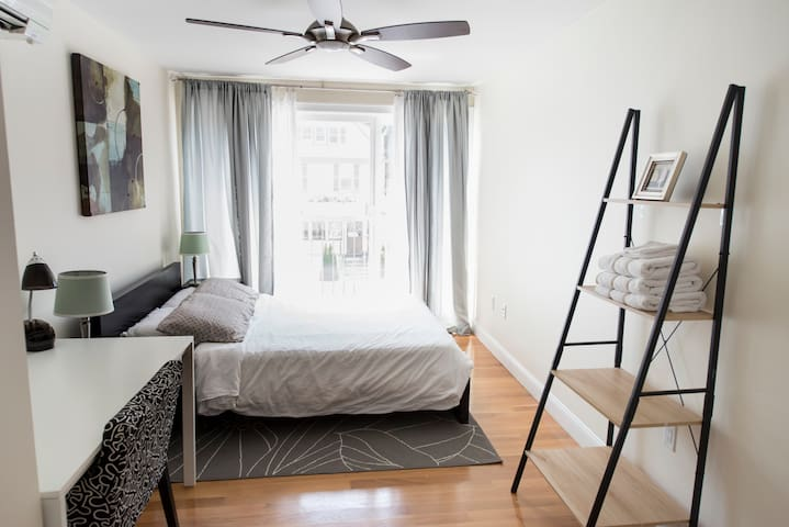The master bedroom features a modern ceiling fan and shelf space for your personal belongings