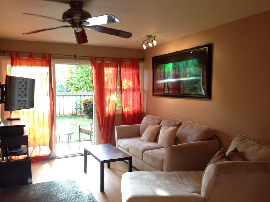 Spacious Living Room with high end art and Sleeper sofa looking out towards beautiful garden setting.