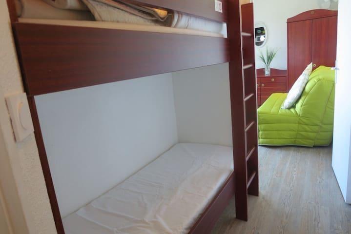 dans la cabine en entrant dans le studio, les lits superposés 75 x180 cm.  nb. L'armoire à l'arrière plan est un ancien meuble. Elle a été remplacée par les meubles en bois massif clair des autres photos;